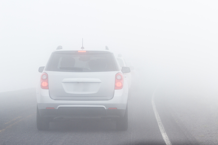 Photo for view of a car driving on a paved road with extremely limited visibility due to heavy fog - Royalty Free Image