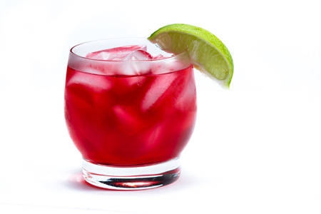 Photo pour close up of a red cocktail served on the rocks garnished with a lime isolated on a white background - image libre de droit