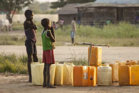 Foto de BOR, SOUTH SUDAN-NOVEMBER 1 2013: Unidentified children wait for the water to turn on at a central water point in Bor, South Sudan - Imagen libre de derechos