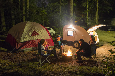 Photo for Family of five camping at night with campfire - Royalty Free Image