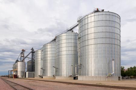Foto de Round metal grain elevator bins next to railroad tracks in the United States. - Imagen libre de derechos