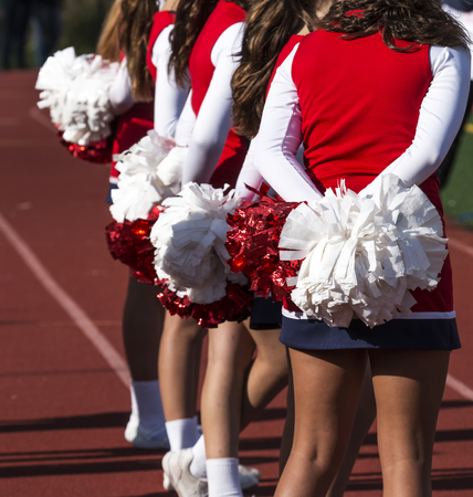 Photo pour A few cheerleaders watch the football game rooting for their home team. - image libre de droit