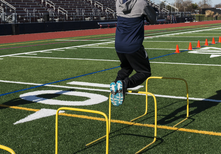 Photo pour A track and field athlete jumping over yellow mini hurdles on a turf field from behind the runner. - image libre de droit