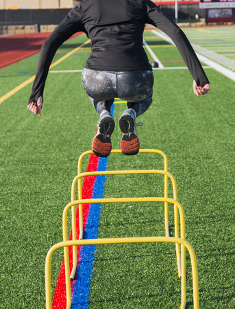 Photo for A high school track and field sprinter is jumping over yellow banana hurdles for strength and stability during practice on a green turf field on a cool afternoon. - Royalty Free Image