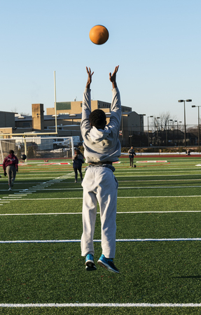 Photo for A male high school track and field athlete throwing a medicine ball in the air and jumping off of the ground during speed training drills. - Royalty Free Image