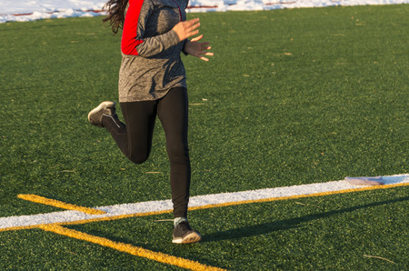 Photo pour A high school female runner is running fast on a green turf field iin the winter, with snow lining the track behind her. - image libre de droit