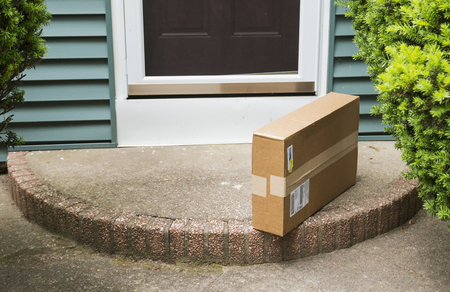 Photo for A brown cardboard box is left on the front stoop after being delivered while no one was home. - Royalty Free Image
