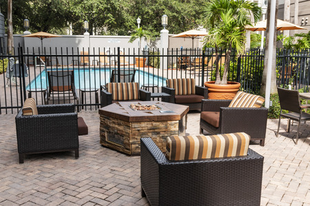 Photo for The patio of a hotel it set up with a ire pitt, a pool and furniture to relax during your stay. - Royalty Free Image