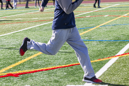 Photo pour A high school sprinter is running on a green turf field during winter track and field practice. - image libre de droit