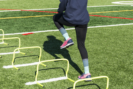 Photo for A female high school track and field runner is performing running and coordination drills by stepping over two foot yellow mini hurdles. - Royalty Free Image