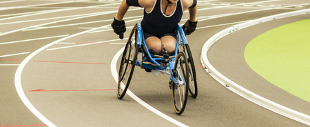 Photo pour A high school girl in a wheelchair is racing the mile on an indoor track. - image libre de droit