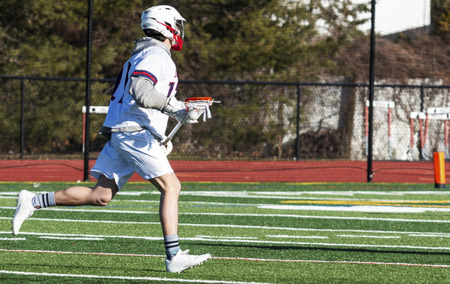Photo pour A high school boy lacrosse player is running doen the field with the ball in the net of his stick looking to make a play. - image libre de droit