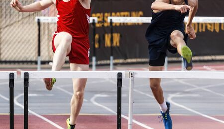 Photo for Two high school boys are tied in the 400 meter hurdle race entering the final straightway. - Royalty Free Image