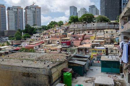 Foto de Colorful illegal houses of the poor inhabitants of Luanda, Angola. These ghettos resemble Brasilian favelas. In the background the high rise buildings of the rich build a stark contrast. - Imagen libre de derechos