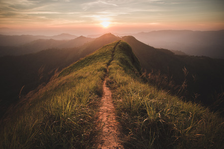Foto de The way of climax. Mountain slope have a way for walk. Background is sunset. - Imagen libre de derechos