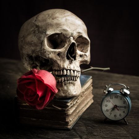 Photo pour Still life with human skull with red rose in the mouth, old book and alarm clock - image libre de droit