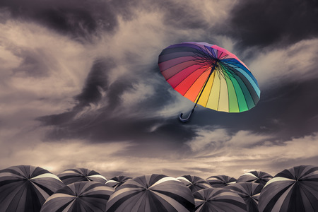 Foto de rainbow umbrella fly out the mass of black umbrellas - Imagen libre de derechos