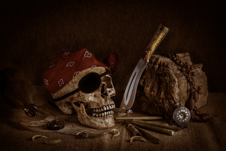 Photo pour Still life, pirate skull with cigar in the mouth, compass on ancient map, knife and pocket watch hang on the log - image libre de droit