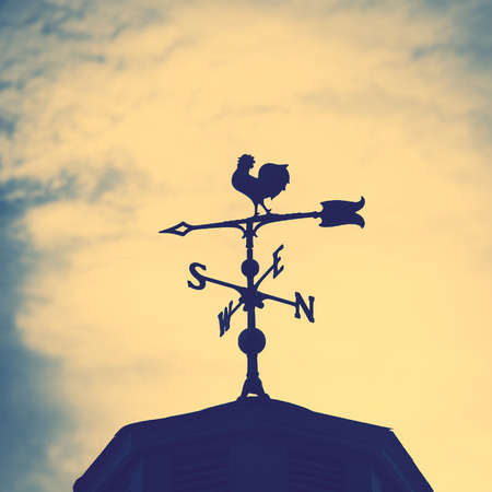 Photo pour Rooster weather vane on a rooftop with an arrow and North-South pointer to show the direction of the wind against a hazy blue sky, vintage style - image libre de droit