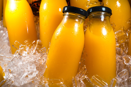 Photo pour Orange juice bottles on the ice box - image libre de droit