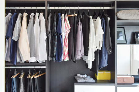 Photo for modern closet with row of cloths hanging in black wardrobe - Royalty Free Image