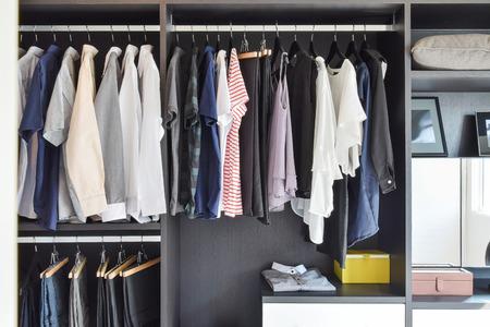 Foto de modern closet with row of cloths hanging in black wardrobe - Imagen libre de derechos