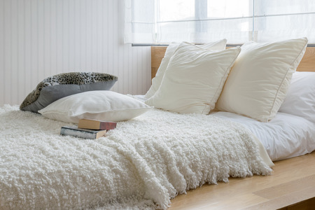 sylish bedroom interior design with black and white pillows on bed.