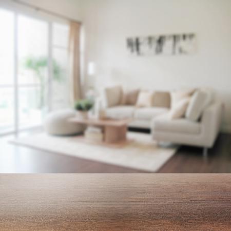 Foto de wooden table top with blur of modern living room interior as background - Imagen libre de derechos