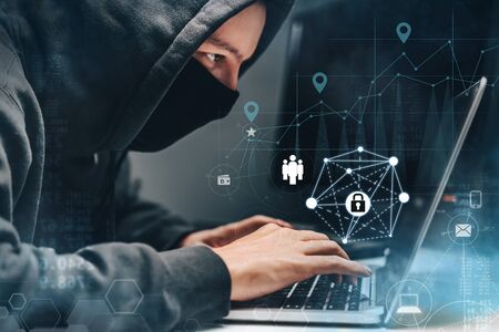 Foto de Man wearing hoodie and mask hacking personal information on a computer in a dark office room with digital background. Cyber crime, deep web and ransomware concept. - Imagen libre de derechos