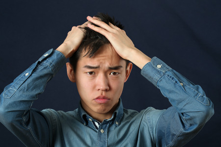 Disappointed young Asian man making face and looking at camera