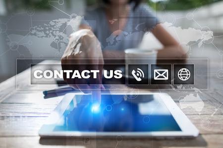 Foto de Contact us button and text on virtual screen. Business and technology concept. - Imagen libre de derechos