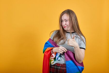 Photo pour Pretty young girl over isolated orange wall wearing fashion clothes celebrating a victory in winner position, keeping fists up covered LGBT flag - image libre de droit