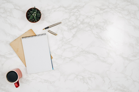Foto de Blank notebook page on white marble table background. Image taken from above, top view. Frame composition with copy space - Imagen libre de derechos