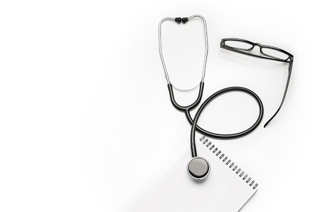 Foto de Stethoscope and prescription notepad isolated on white background. Sterile doctors office desk. Medical accessories on a white table background with copy space around products. Photo taken from above. - Imagen libre de derechos