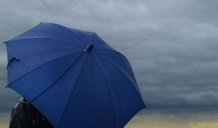 Blue umbrella over a dark stormy cloud