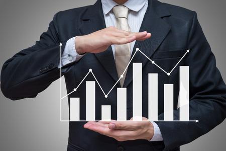 Foto de Businessman standing posture hand holding graph finance isolated on gray background - Imagen libre de derechos