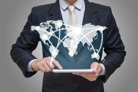 Photo pour Businessman hand holding tablet global marketing on gray background - image libre de droit
