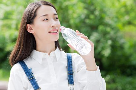 Foto de girl drinking bottled water, asian woman - Imagen libre de derechos