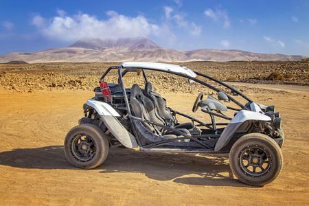 Foto de White buggy in stone and sandy desert on volcanic island Fuerteventura, Canary islands, Spain. In the background is blue sky. - Imagen libre de derechos