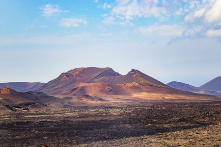 Photo for A View of the red volcanic hill in the sandy desert in Timanfaya National Park. Blue sky with clouds is in the background. It is situated in Lanzarote, Canary islands, Spain. - Royalty Free Image