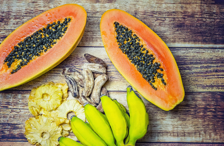 Photo for Fresh papaya, small fresh bananas, dried pineapples and dried small bananas on a wooden background. Everything is organic and imported from Africa. - Royalty Free Image