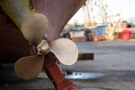 Foto de The screw of a fishing boat exhibited in a port workshop. Repair of damaged fishing boats in the workshop on the port wharf. Autumn season - Imagen libre de derechos