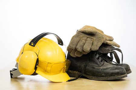 Foto de Protective helmet and work boots on a wooden table. Safety and health protection accessories for construction workers. White isolated background. - Imagen libre de derechos