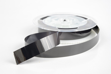 Foto de Old VHS cassette with unwound tape. Damaged data medium for old home picture and sound recording devices. White background. - Imagen libre de derechos
