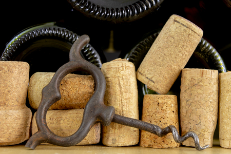 Photo pour A corkscrew for uncorking wine and old corks on a wooden table. Old wine accessories. Light background. - image libre de droit