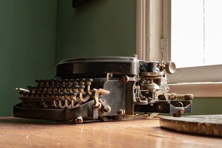 Photo pour An old typewriter on a desk in a household. Accessories for writers in the comfort of your home. Dark background. - image libre de droit