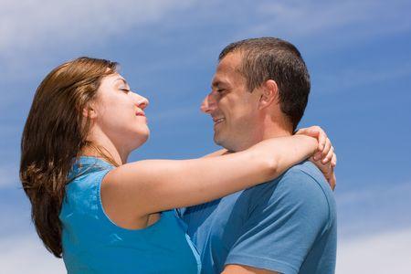 Loving couple under summer blue sky