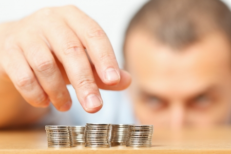 Businessman reaching for pennies, financial crisis or savings concept