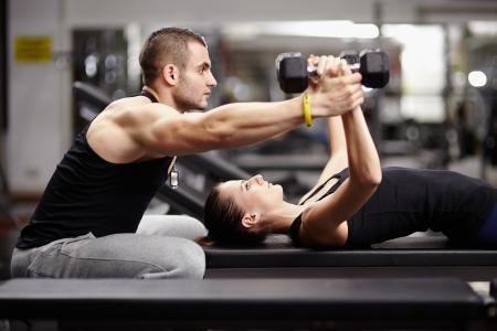 Foto de Personal trainer helping woman working with heavy dumbbells - Imagen libre de derechos