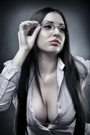 Photo pour Monochrome portrait of a sexy teacher wearing glasses and displaying her cleavage - image libre de droit